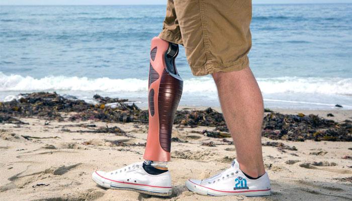 Prothèse de jambe UNYQ imprimé en 3D porté par un homme sur la plage